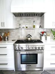 white glass tile backsplash countertop with dark wood cabinets
