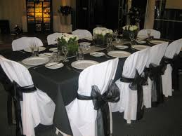 Black Table Centerpieces by Black Table Cloth White Dishware White Chair Cover Black Ribbon