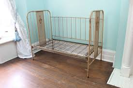 furniture antique iron baby daybed placed on brown laminate