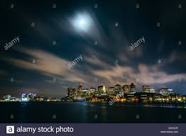 the moon and clouds moving through the sky the boston skyline