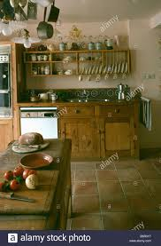 large old butchers block in country kitchen with terracotta tiled large old butchers block in country kitchen with terracotta tiled floor and dishwasher in old fitted pine cupboards