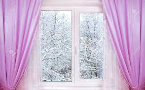window with pink curtains and winter view behind it stock photo