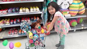 kid shopping for easter eggs with doll at the store