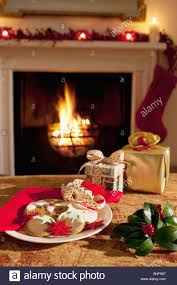 christmas gifts and cookies near fireplace stock photo royalty