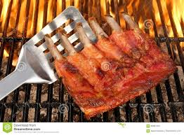 baby back or spare ribs on the flaming bbq grill stock photo