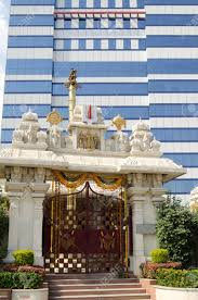 a hindu temple beside a modern office block in hi tech city