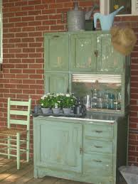 green hoosier cabinet on back porch to be repurposed into a coffee