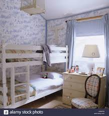 blue toile de jouy wallpaper in bedroom with blue floral quilt on bunkbed and toile de jouy wallpaper in bedroom of english country house stock photo