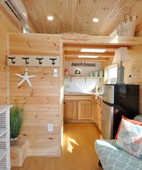 harbor by tiny house building company hickory cabinets flush the kitchen is equipped with an induction cooktop large sink refrigerator and hickory cabinets
