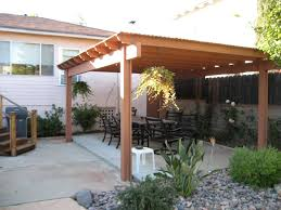 exterior brown wooden covered patio overed black metal dining