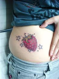 strawberry with stars tattoo on side rib by eric agathon