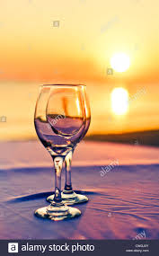 two wine glass with sunset background for romantic or luxury
