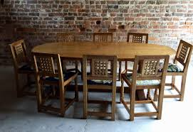 vintage solid oak dining table and eight chairs by robert mouseman