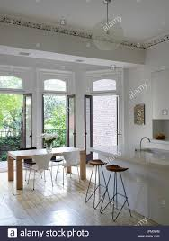 breakfast bar stools and small dining table in white kitchen with