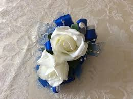 corsage and matching boutonniere in white roses and royal blue
