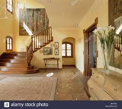terracotta tiles on floor in long corridor with beamed ceiling and