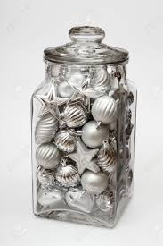 glass jar filled with silver decorations on white stock