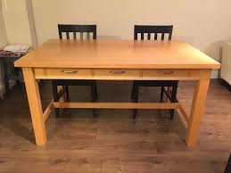 beech veneer dining table with 4 navy dining chairs in tooting