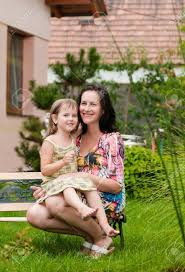 portrait of mother with daughter siting on bench in garden