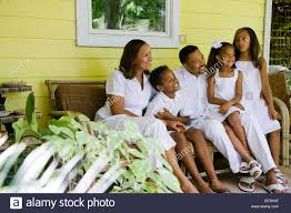 happy african american family sitting on bench on front porch of