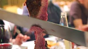 closeup of a picanha meat cutting on the blade in brazilian