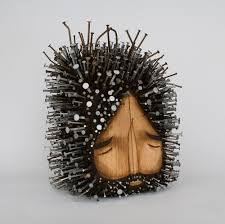 figurative found wood sculptures pierced with hundreds of nails by
