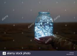 is holding lights in a jar on winter landscape stock