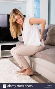 canap mal de dos femme souffrant de mal de dos assis sur un canapé à la maison