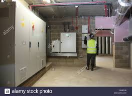 an engineer inspects the switchgear in the basement plant room of