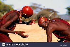 two maasai young men painting their heads with red ochre stock