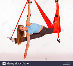 young woman upside down doing anti gravity aerial yoga in hammock
