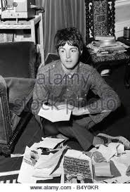 paul mccartney of the beatles sitting on the floore cross legged