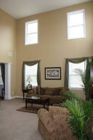 Rich Gold Walls Are Complimented With White Cabinets And Warm - Brown paint colors for living room
