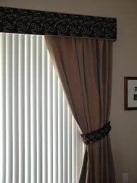 cornice with one way draw drapes and vertical blinds on glass