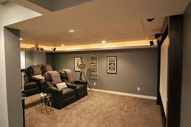 contemporary home theater design white screen on grey wall with black leather chair and round table