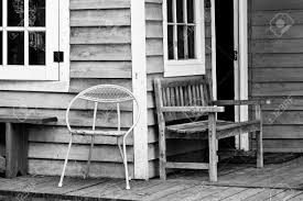 a bright yellow metal chair on the porch of an old bungalow stock