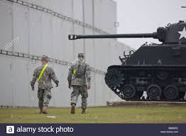 two u s army soldiers walk past a tank on display at fort a