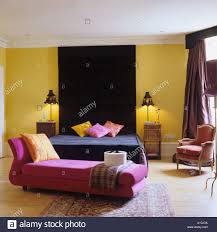 Pink And Black Bedrooms Pink Chaise Longue And Black Bed In Yellow Bedroom Stock Photo