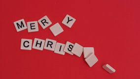 letter tiles moving to spell merry on background stock