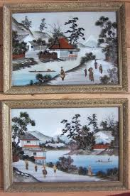 a set of landscape oil paintings inlaid with mother of pearl in frames behind glass