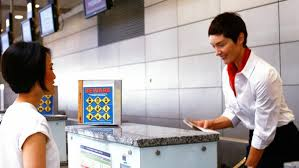 female airport staff checking passport at airport check in desk