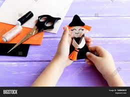 holds a halloween witch doll in his hands and shows it scissors