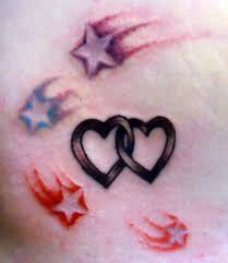 black hearts and red stars tattoo on forearm