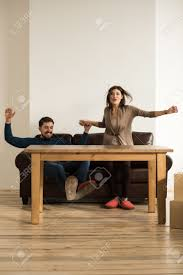 front view of happy young couple placing sofa and table in living