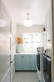 blue laundry room cabinets with white countertops transitional