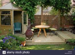 Gardens With Summer Houses - a small wooden summer house with chairs a table and a green stock