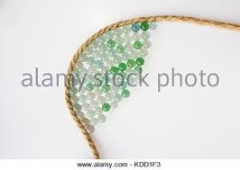 many small glass balls and a jute rope on a white background stock