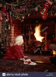 1960s small blonde by fireplace decorated for christmas