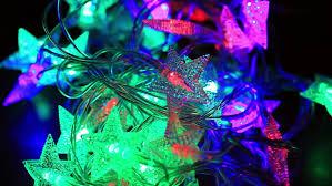 tangled christmas light bulbs stars shape on black background