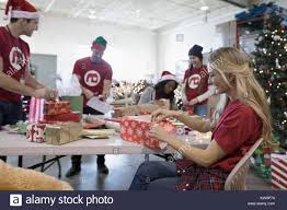 Christmas Gifts For Volunteers Volunteers Wrapping Christmas Gifts In Warehouse Stock Photo